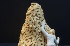 Escultura: un hombre escalando una montaña de letras