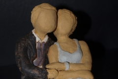 Escultura: pareja abrazada y sentada