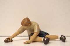Escultura: Niño jugando en el suelo