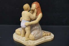 Escultura: Madre sentada jugando con su bebé